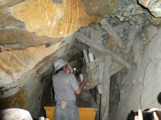 Der Arbeiter belädt die Lore, das Erz kommt in Holzboxen nach unten